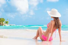 Back view of long haired girl in bikini and straw hat on tropical caribbean beach Stock Image