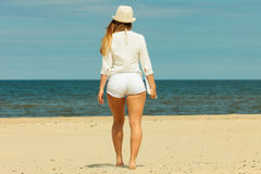 Back view of long haired woman on beach. stock photos