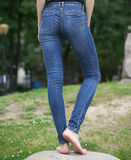 Back view of a long women legs posing with jeans Stock Image