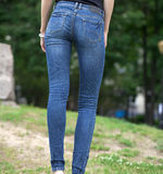 Back view of a long women legs posing with jeans Royalty Free Stock Image