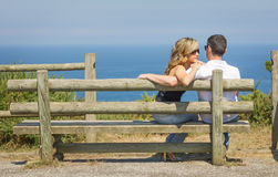 Back view of love couple sitting outdoors on bench Royalty Free Stock Photos