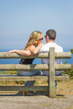 Back view of love couple sitting outdoors on bench Stock Photography