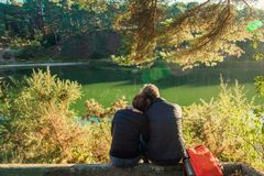 Back view of lovely couple man and woman sitting near forest lake hugging and relaxing. Love Emotions Outdoor concepts. Idyllic. Calm peaceful persons, freedom stock photo