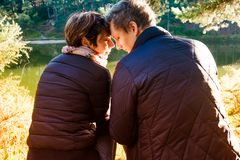 Back view of lovely couple man and woman sitting near forest lake hugging and relaxing. Love Emotions Outdoor concepts. Idyllic. Back view of lovely couple men royalty free stock photography