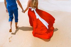 Back view of loving couple walking away with footprints at sandy beach. Holding hands. Back view of loving couple holding hands. Lovers walking away with Royalty Free Stock Image
