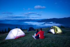 Back view, loving people sitting near camping enjoying sunrise in mountains. Back view, loving people sitting near camping enjoying sunrise in the mountains. In stock photography