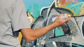 A hand shakes a paint can near a graffiti wall. A back view on a male arm shaking a spray paint can stock footage