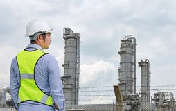 Back view of Male construction worker against gas separation plant.  stock photo