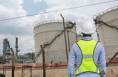 Back view of Male construction worker against gas separation plant.  royalty free stock images
