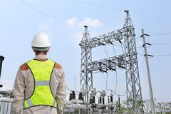 Back view of Male construction worker against power plant background.  royalty free stock images