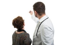 Back view of male doctor pointing to female patient with marker stock image