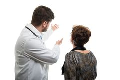Back view of male doctor showing to female senior patient royalty free stock photo