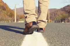 Back view of male feet walking wearing autumn shoes. Back view of male feet walking and wearing autumn real or genuine leather shoes in the middle of an asphalt Royalty Free Stock Photos