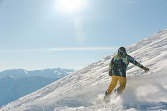 Back view of male freeride snowboarder sliding down the snowy hill. Back view of male freeride skier dressed in sportswear sliding down the snowy hill against Royalty Free Stock Images