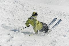 Back view of male freeride skier sliding down the snowy hill. Back view of male freeride skier dressed in green sportswear sliding down the snowy hill Royalty Free Stock Photography