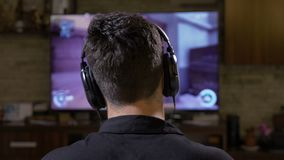 Back view of male gamer guy wearing headphones playing fps action shooter video game on TV console at home -. Back view of male gamer guy wearing headphones stock footage