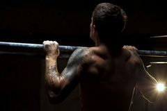 Back view of male muscular adult pulling up. Fitness, gymnastics workout in gym Royalty Free Stock Image