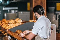 Back view of male shop assistant arranging fresh bread. In supermarket Stock Image