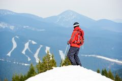 Back view of male skier enjoying on the top of the slope at ski resort. Mountains, forests and ski slopes on the background. Ski season and winter sports Stock Images