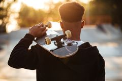 Back view of a male teenager guy holding skateboard. On shoulders while standing outdoors Royalty Free Stock Photo