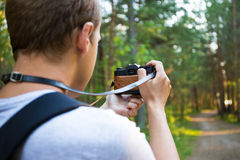 Back view of man with backpack taking a photo in forest Royalty Free Stock Photos