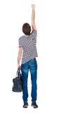 Back view of  man with bag.  Raised his fist up in victory sign. Royalty Free Stock Image