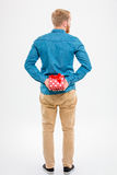 Back view of  man with beard holding red gift Royalty Free Stock Images