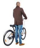 Back view of a man with a bicycle. Royalty Free Stock Photo
