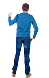 Back view of  man in blue pullover shows thumbs up. Royalty Free Stock Photography