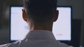 Back view Man browsing Internet Sites on Computer Monitor. Web Pages Surfing, Concept of searching for information on. Back view Man browsing Internet Sites on stock footage