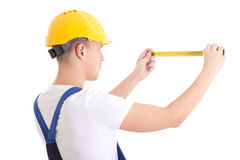 Back view of man builder in blue coveralls holding measure tape Stock Images
