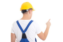 Back view of man in  builder uniform and helmet pointing at some Stock Photography