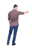 Back view of  man in checkered shirt shows thumbs up. Royalty Free Stock Image