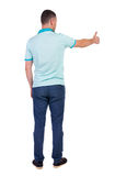 Back view of  man in checkered shirt shows thumbs up. Royalty Free Stock Images