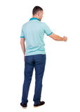 Back view of  man in checkered shirt shows thumbs up. Royalty Free Stock Photography