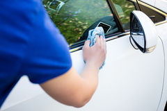 Back view of man cleaning car with microfiber cloth. Back view of man cleaning car with blue microfiber cloth Royalty Free Stock Photos