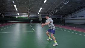 Back view of man dressed in white sport outfit serving and returning bouncing balls with racket. Professional sport