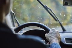 Back view of a man driving a car with moving windshield wipers during rain.  stock photos