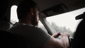 A back view of a man driving a car in the rain. Hands on a steering wheel, wipers working. stock video footage