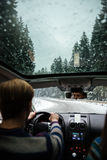 Back view of man driving at car in snowy weather Stock Images