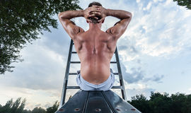 Back view of a man exercising on bench Stock Image
