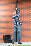 Back view of a man fixing gutters. Vertical Royalty Free Stock Images
