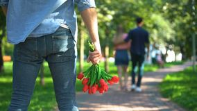 Back view man with flowers watching his girlfriend dating with another male