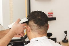 Back view of man getting short hair trimming at barber shop with clipper machine. Back view of man getting short hair trimming at barber shop with a clipper royalty free stock image