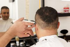 Back view of man getting short hair trimming at barber shop with clipper machine stock photos
