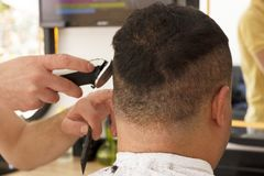 Back view of man getting short hair trimming at barber shop with clipper machine stock photography
