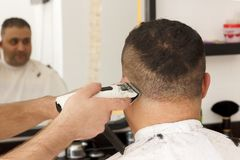 Back view of man getting short hair trimming at barber shop with clipper machine royalty free stock image