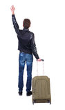 Back view of man with green suitcase greeting waving. Back view of man with  green suitcase man greeting waving from his hands. Rear view people collection Stock Photos