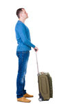 Back view of man with  green suitcase looking up. Royalty Free Stock Photography
