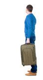 Back view of man with  green suitcase looking up. Stock Image